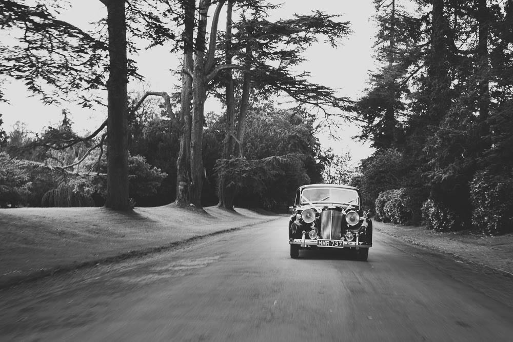 Black and white image of wedding car coming down drive at Grittleton House