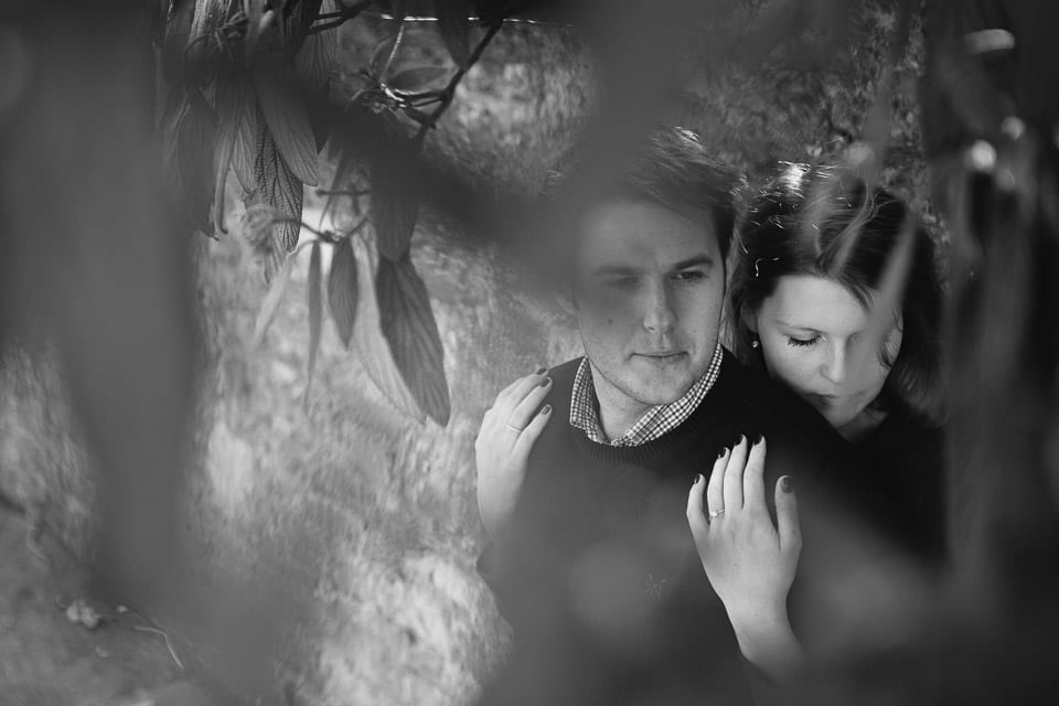 Black and white image of engaged couple hugging under a tree near Lacock