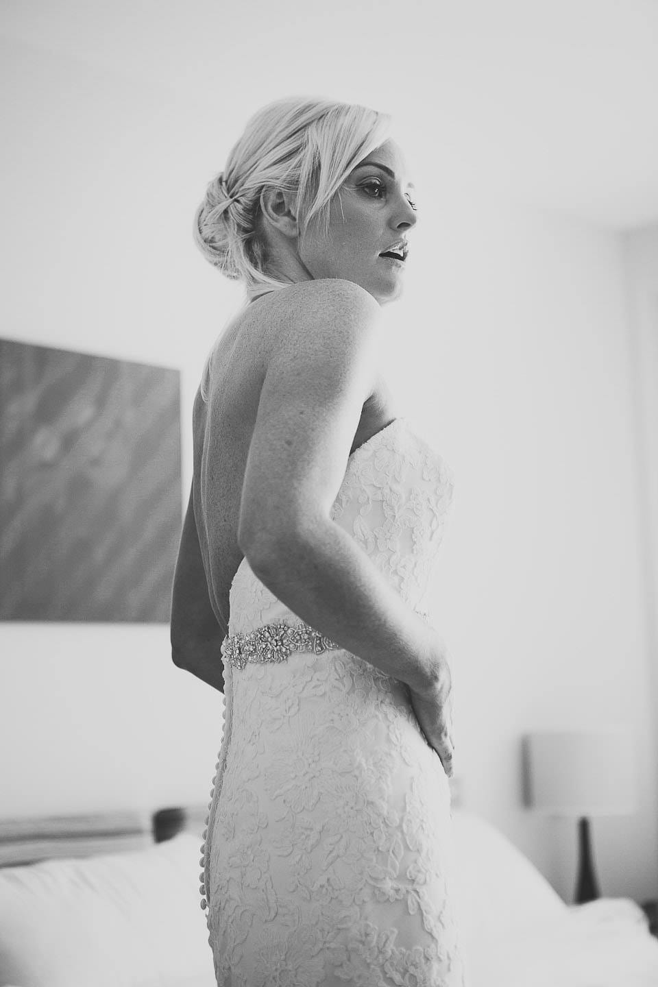 Black and white image of bride looking at her dress in the mirror