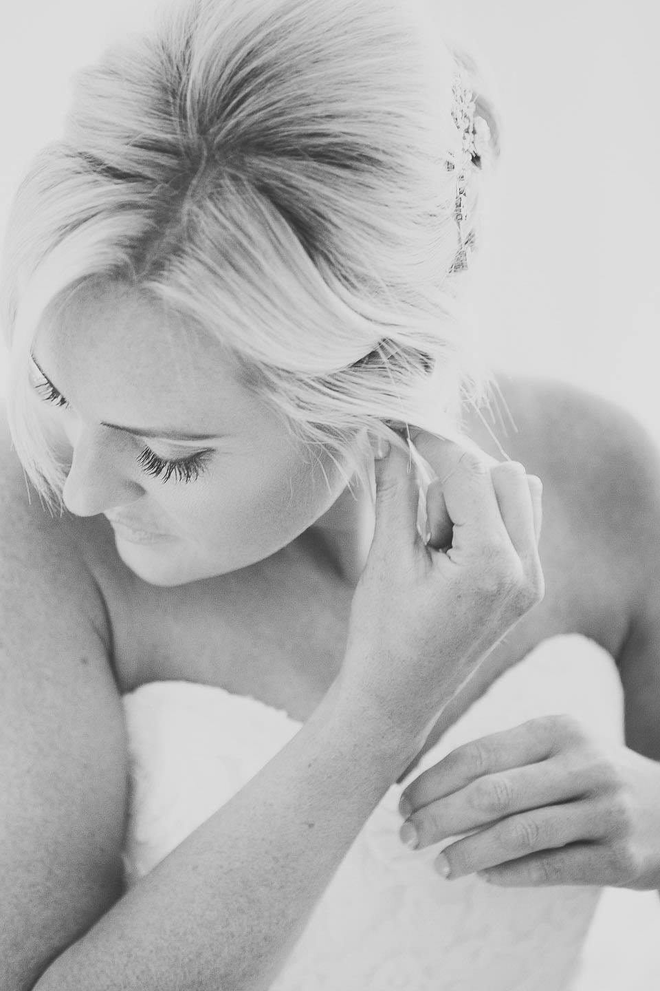 Black and white image of bride putting her earrings in at The Captains Club Hotel