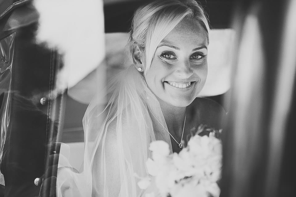 Black and white portrait of bride in wedding car at Sopley Mill