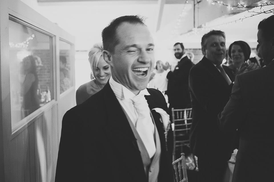 Groom winking at the camera as they come into their wedding breakfast at Sopley Mill