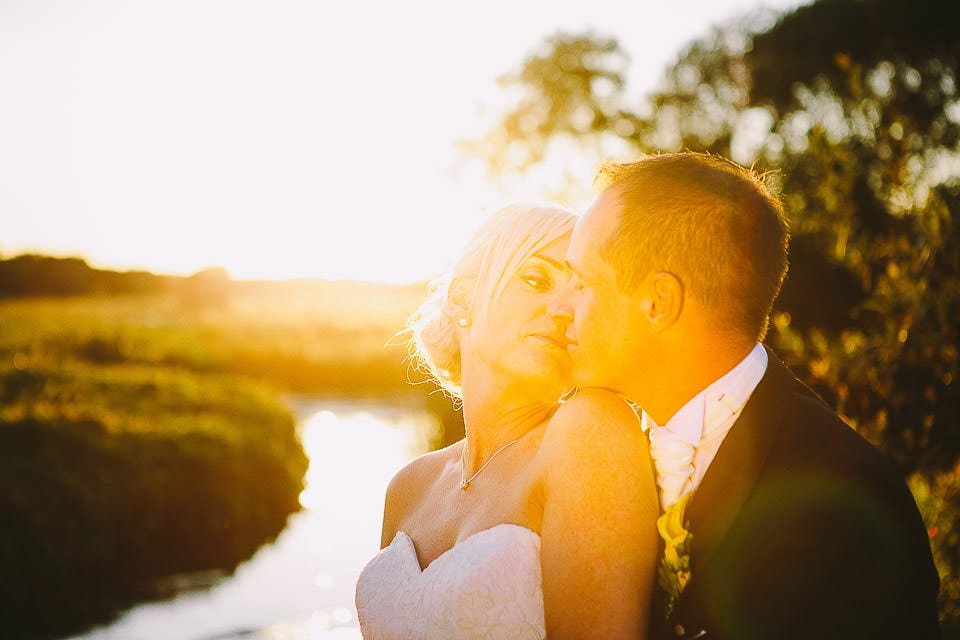 Sunset image of bride and groom kissing in the gardens at Sopley Mill