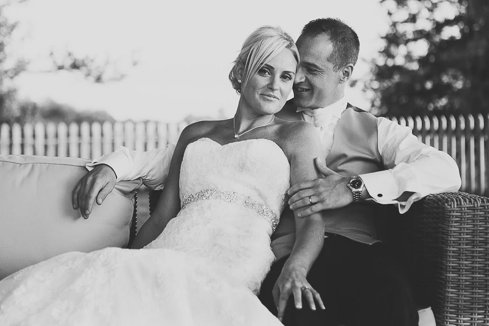 Bride and groom sitting on the sofa outside at Sopley Mill