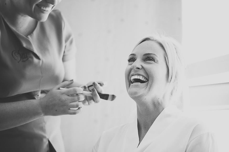 Bride laughing while chatting to make up artist at The Captains Club Hotel