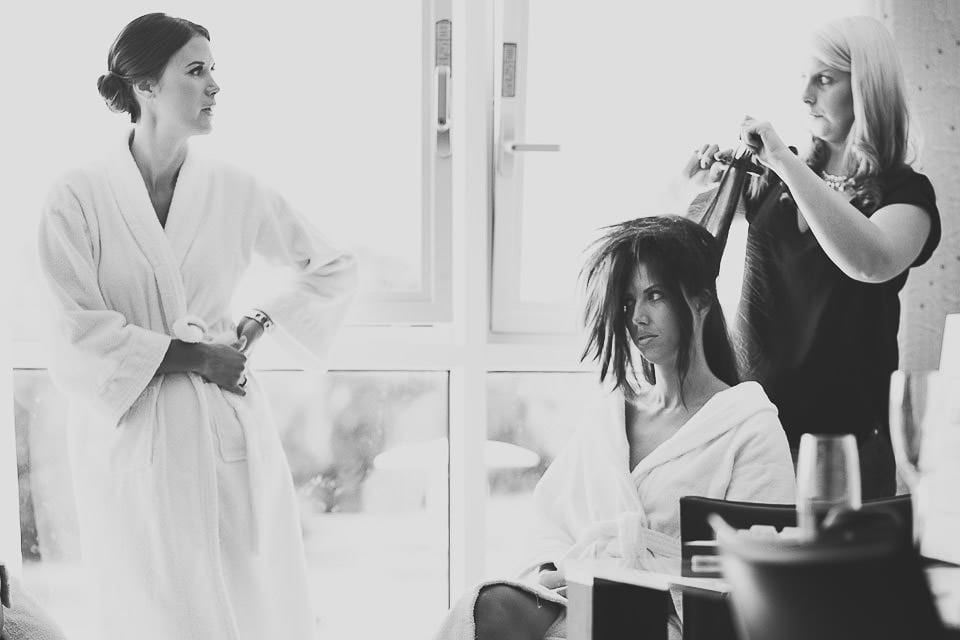 Black and white image of bridesmaids having their hair done at The Captains Club Hotel