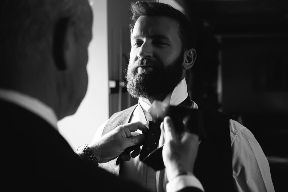 Black and white image of grooms brother having his tie done