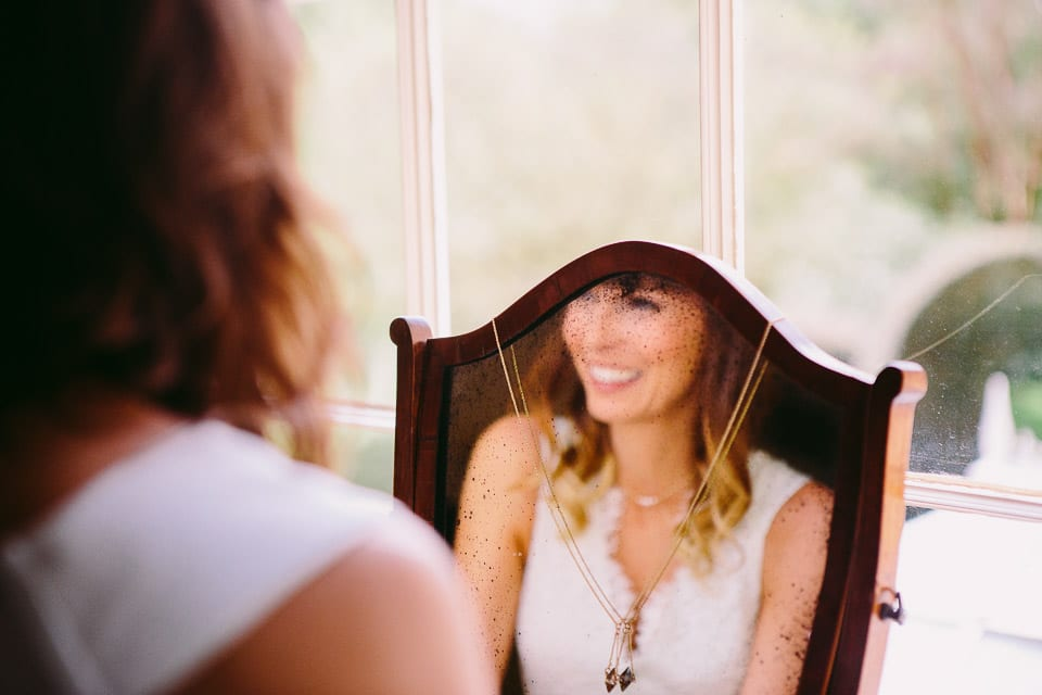 Image of bridesmaid reflected in mirror