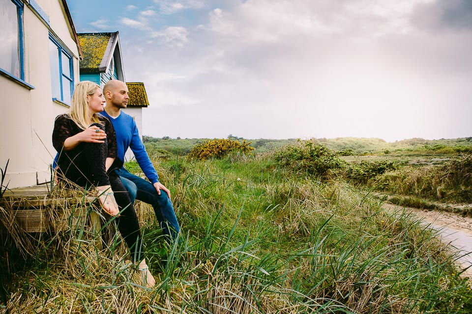 Engaged couple sitting on the verandah of a beach hut at Hengistbury Head