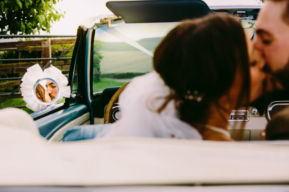 Reflection of bride and groom kissing in wedding car wing mirror