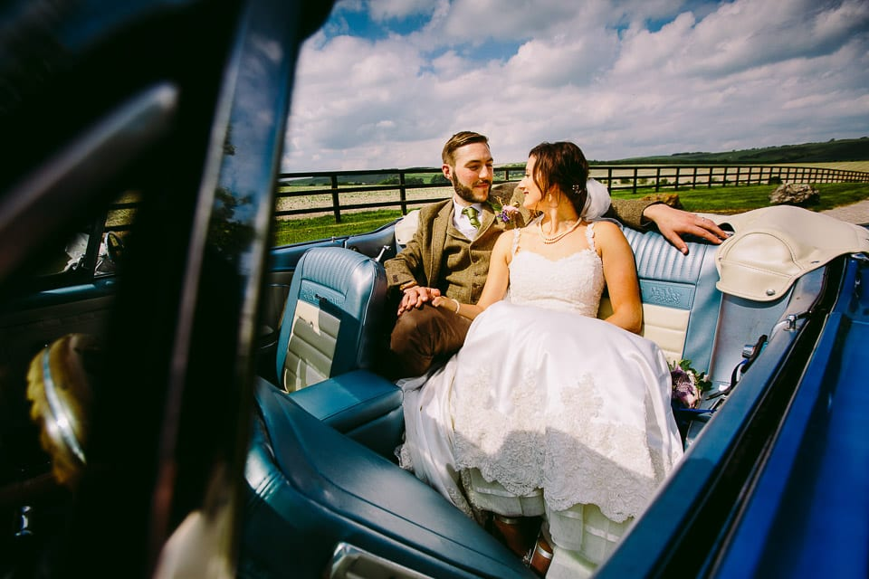 Bride and groom sitting in Ford Mustang wedding car