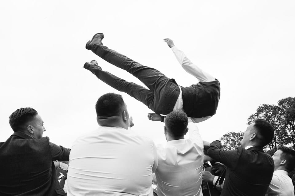 Black and white photo of groomsmen and friends throwing groom into the air