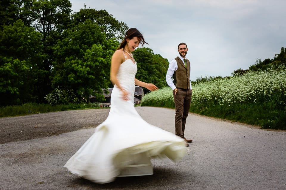 Bride twirling around in her dress while groom looks on