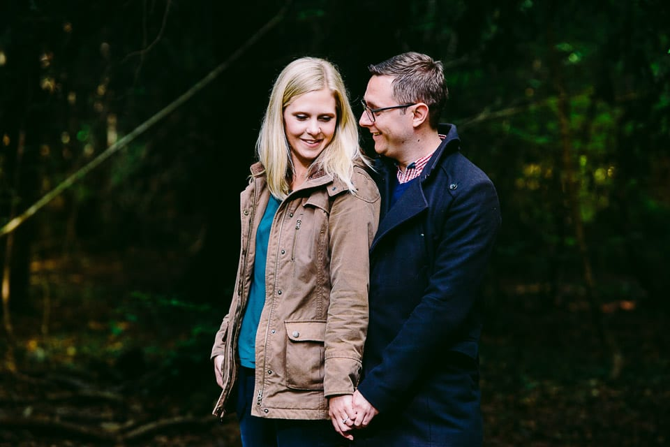 Engaged couple holding hands in Leigh Woods