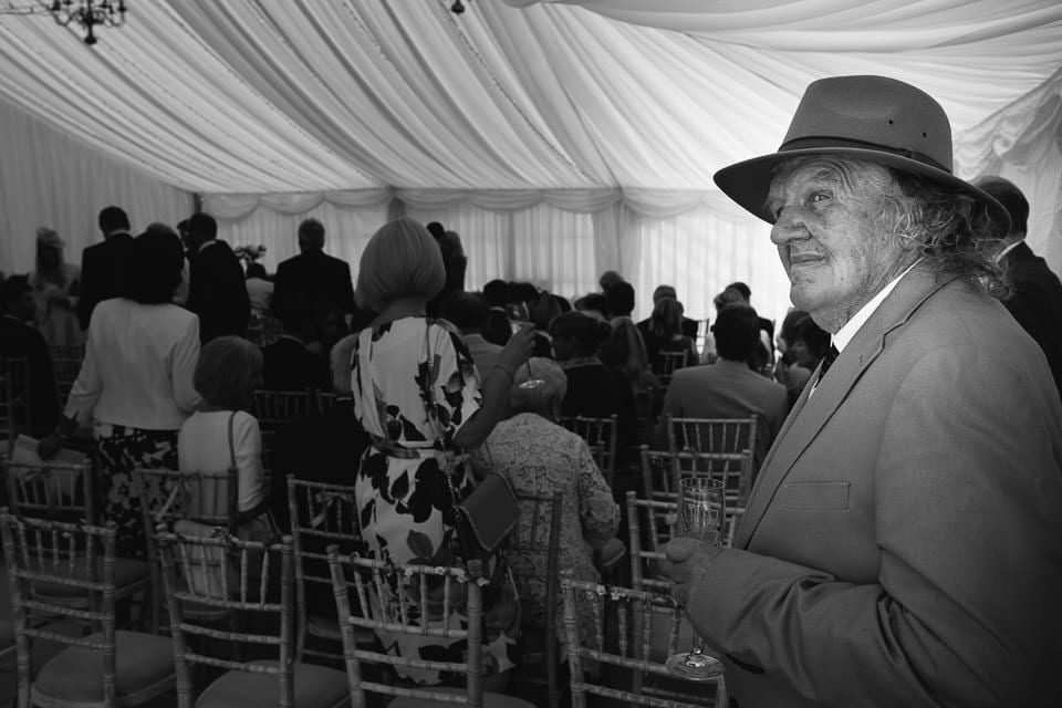 Black and white image of guest in hat before ceremony