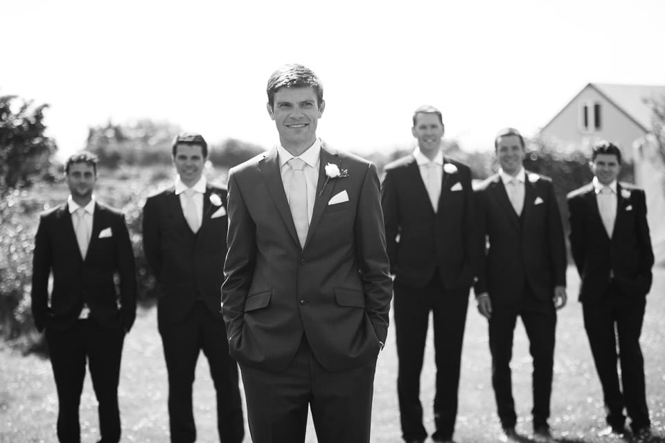 Black and white image of groom with his groomsmen