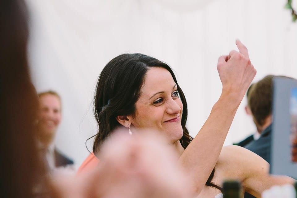 Bride making gesture during grooms speech