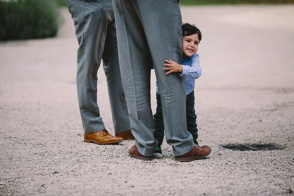 Young boy holding onto his fathers legs
