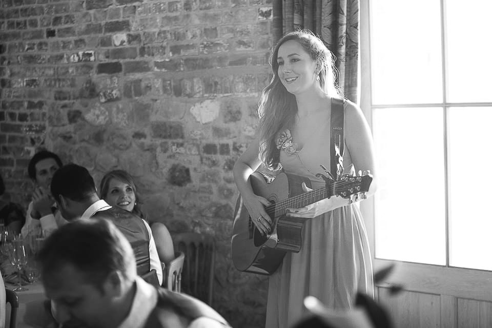 Black and white image of wedding guest singing during wedding breakfast