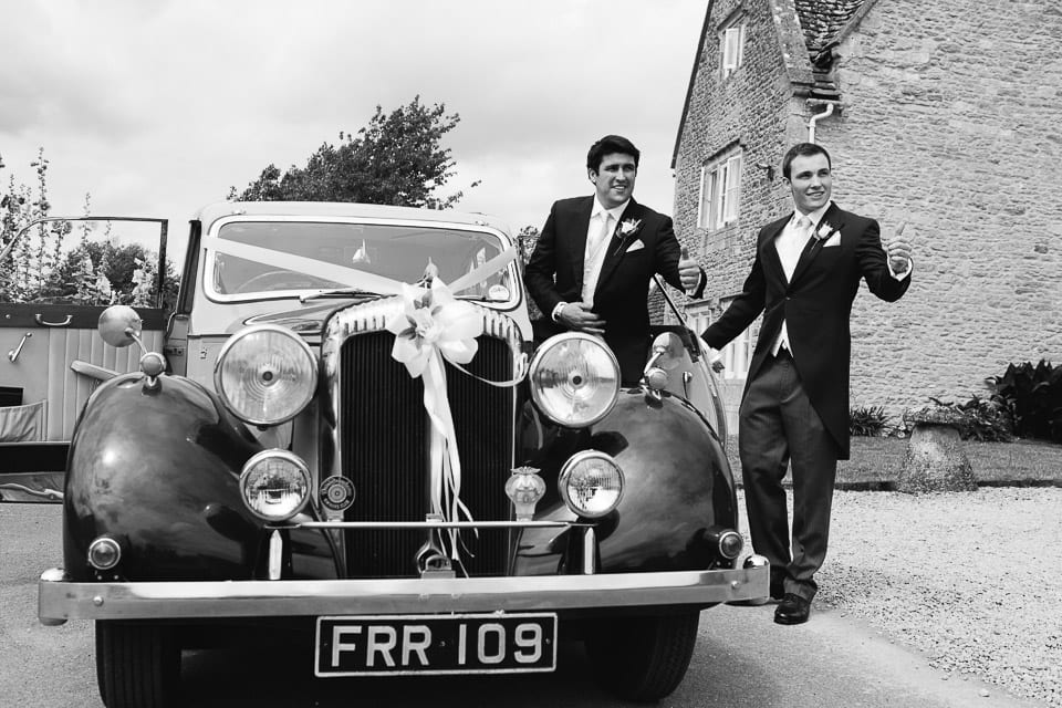 Black and white image of groom and wedding car