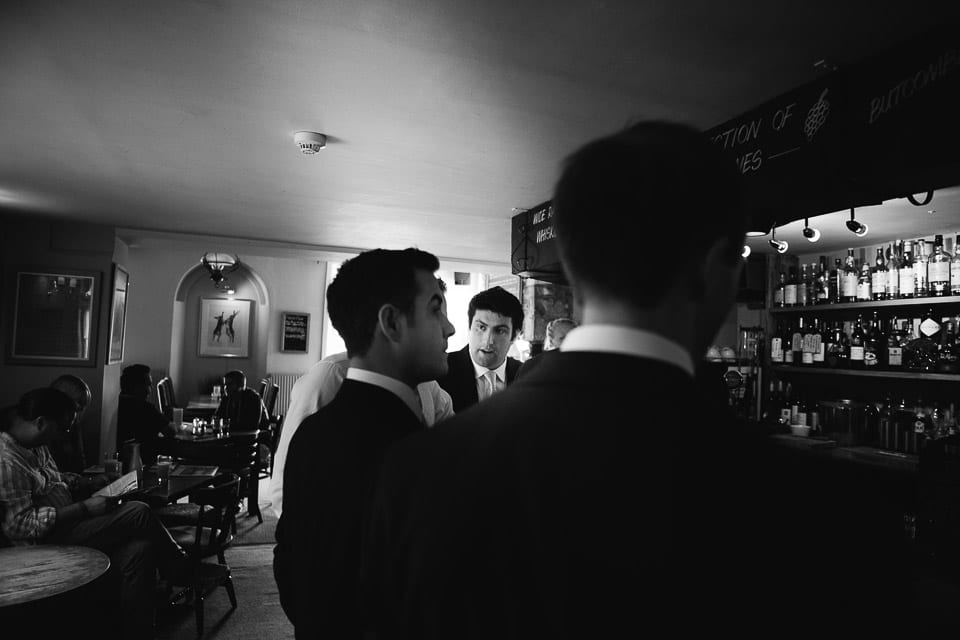 Black and white image of groom and groomsmen in pub