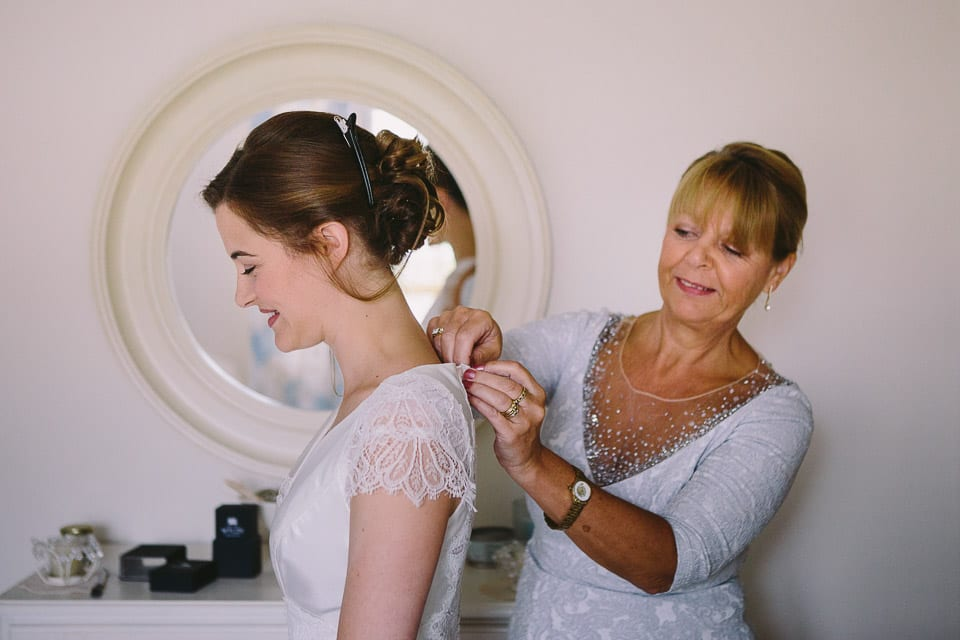 Brides mother buttoning up brides wedding dress