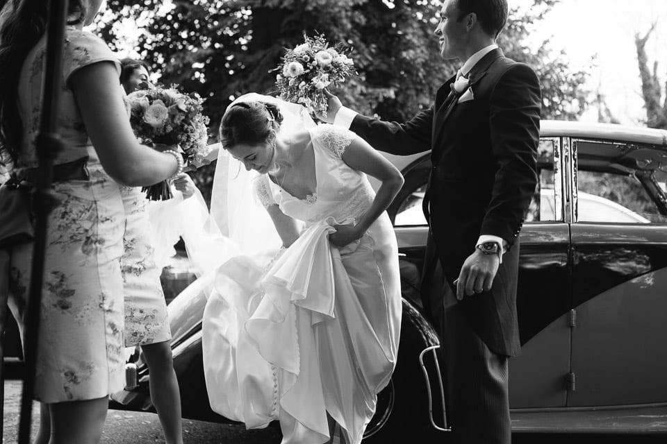 Black and white image of bride getting out of car