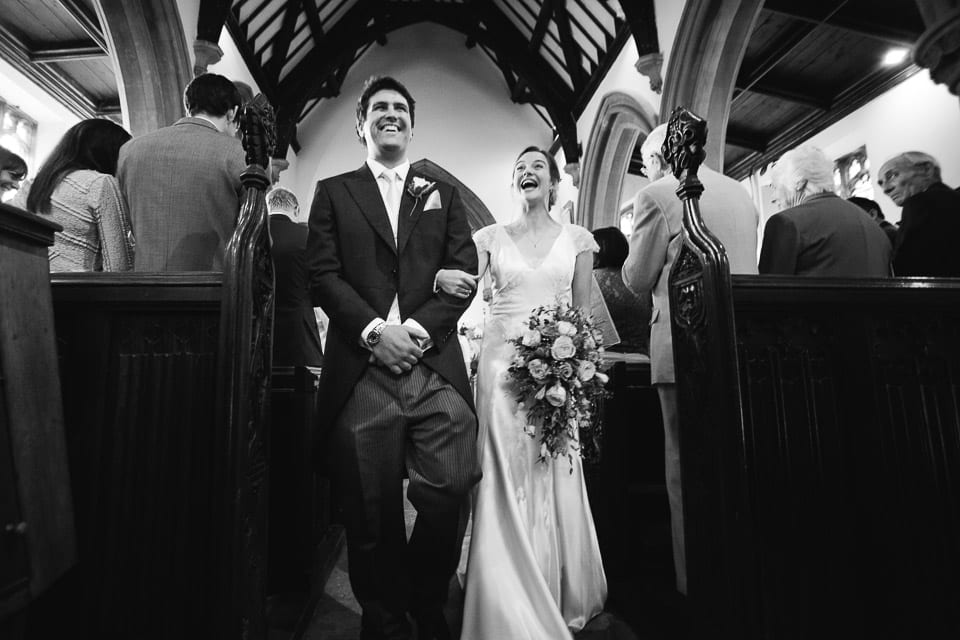Black and white full length of bride and grooms exit from church