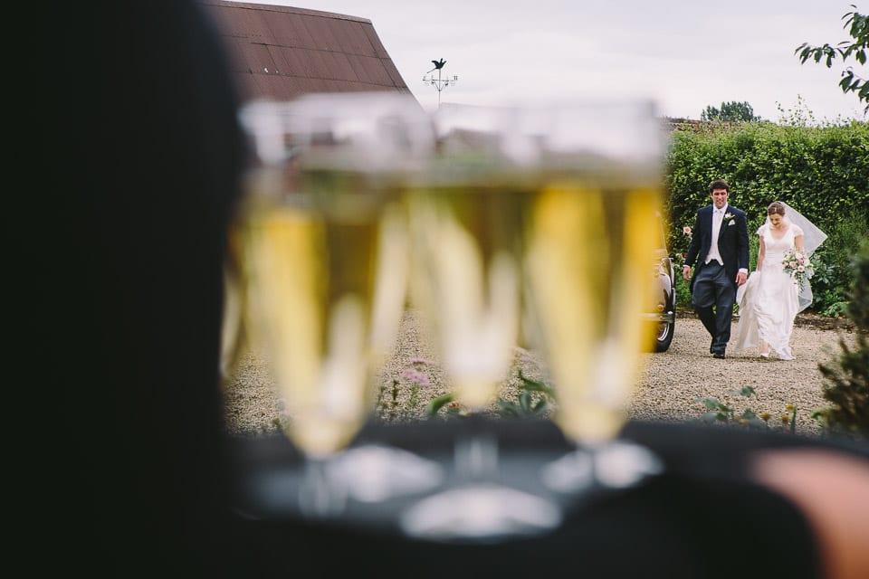 Image of bride and groom in distance through champagne glasses