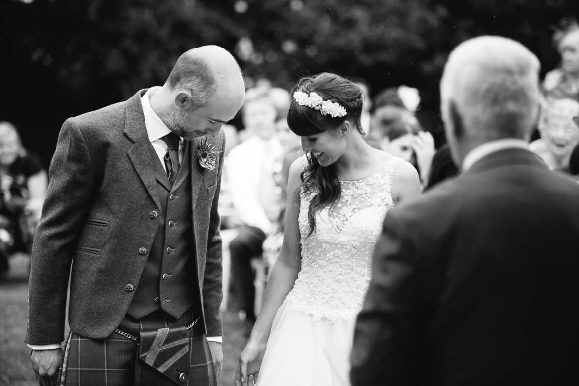 Black and white image of bride and groom during ceremony