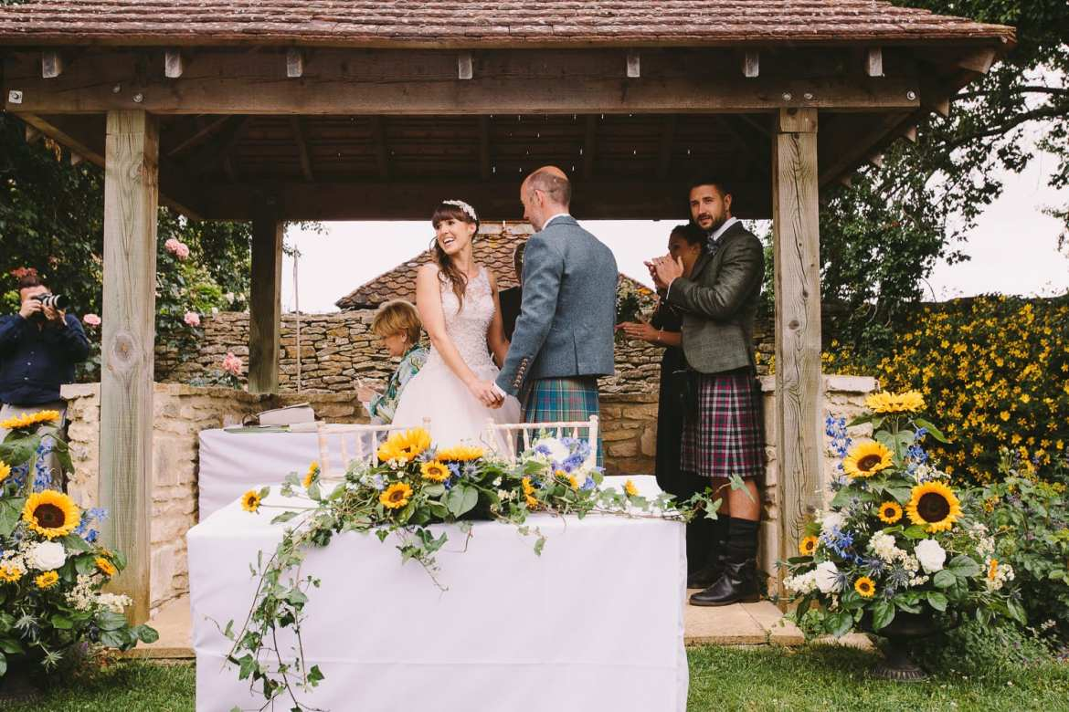 Bride and groom under pavillion in outdoor ceremony