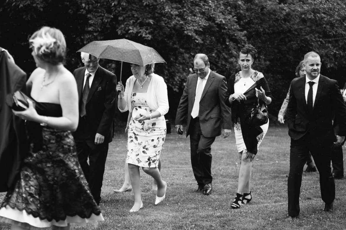 Black and white image of guests running inside due to rain