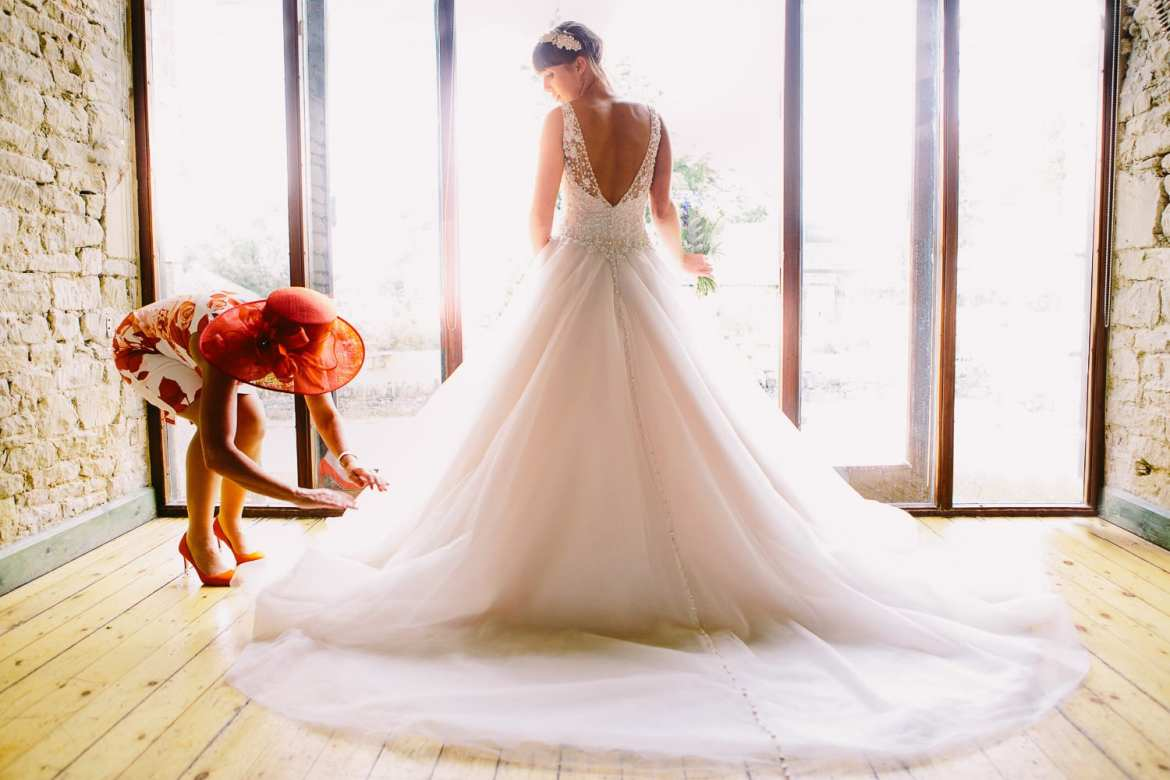 Brides mother arranging brides dress in front of large window