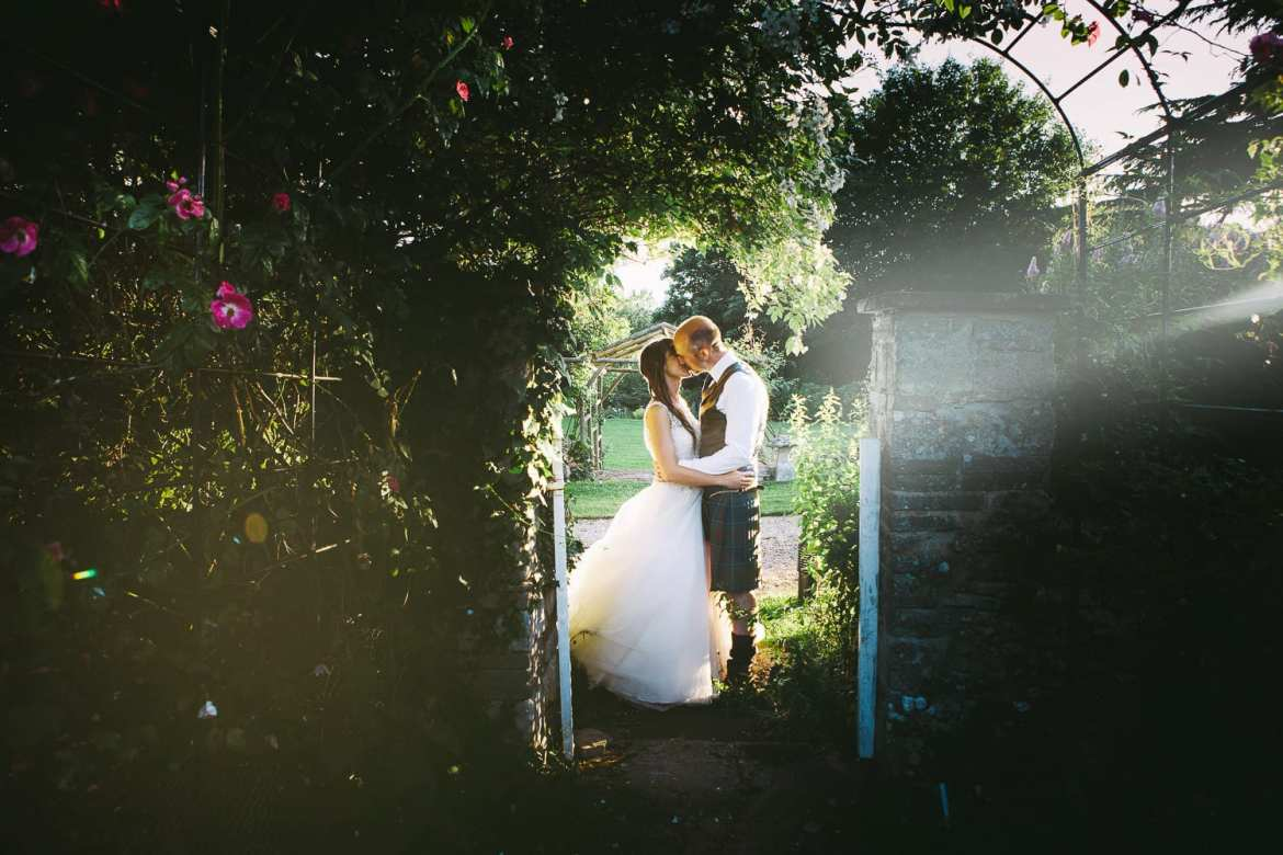 Bride and groom in archway in gardens