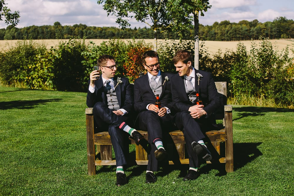 Groomsmen relaxing on a bench in the sunshine at Cripps Stone Barn