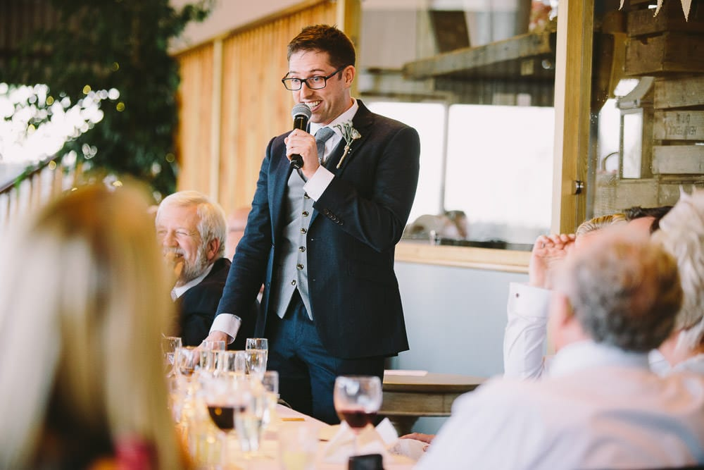 Best man doing his speech in the Dutch barn at Cripps Stone Barn