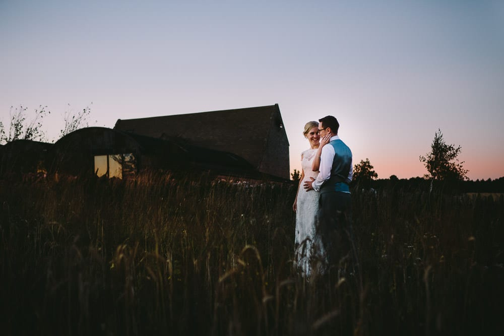Bride and groom at sunset in the field next to Cripps Stone Barn
