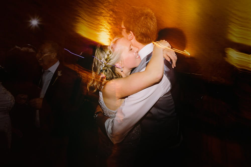 Bridesmaid hugging her other half on the dance floor at Cripps Stone Barn