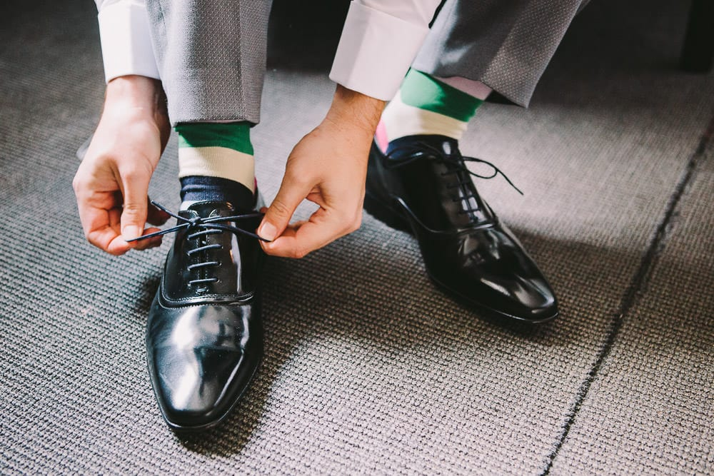 Groom tying his shoelaces at The Wheatsheaf Inn
