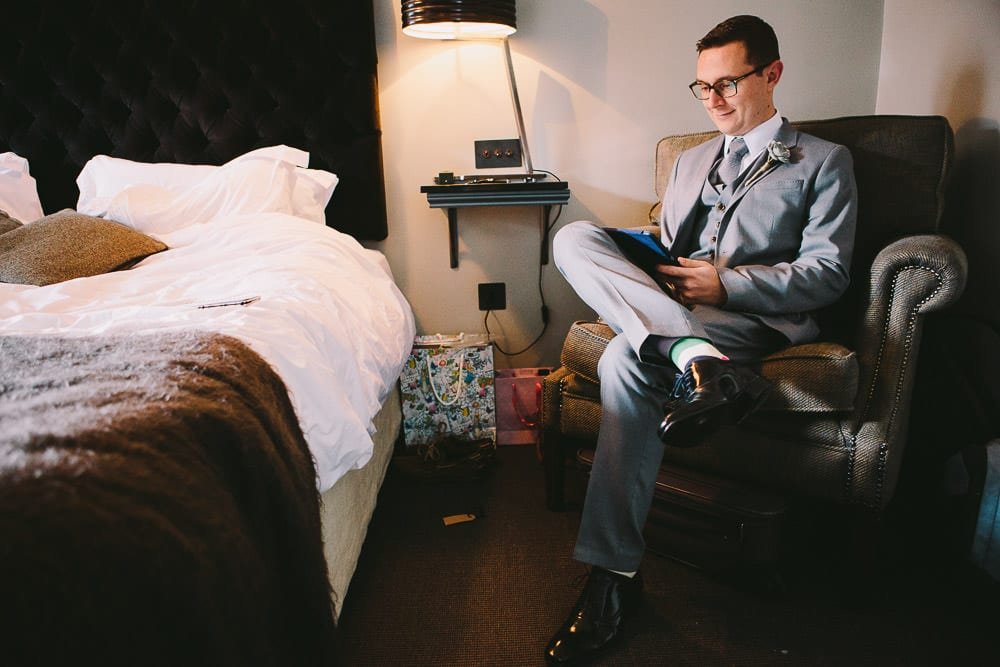 Groom reading through his speech in his hotel room at The Wheatsheaf Inn