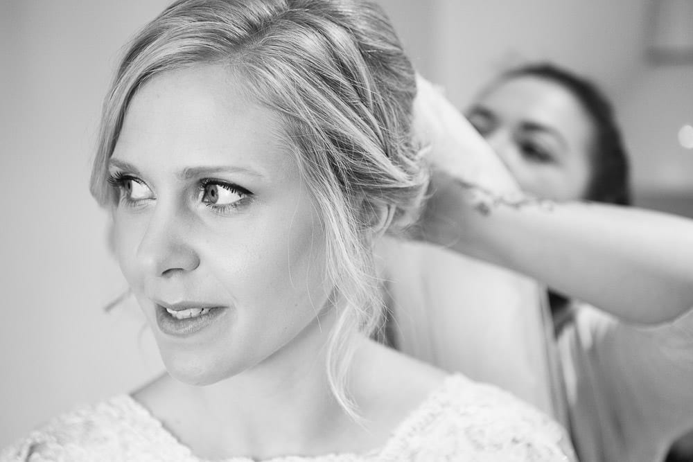 Black and white image of bride having her veil fitted at The Wheatsheaf Inn