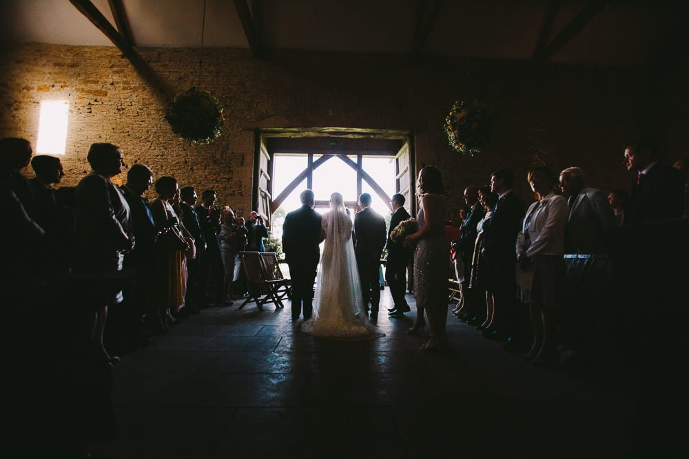 View from behind of the bride and groom with best man and father of the bride at Cripps Stone Barn