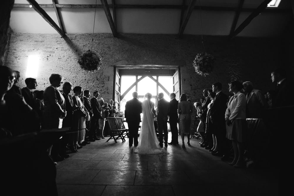 Black and white image of the ceremony from behind at Cripps Stone Barn