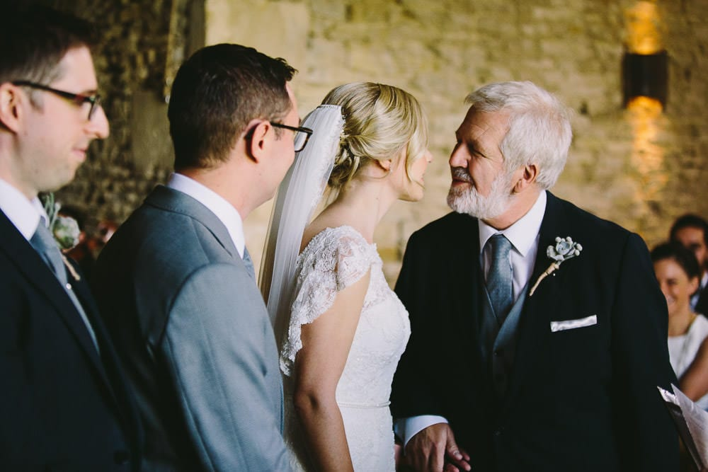 Bride giving her father a kiss before he sits down at Cripps Stone Barn