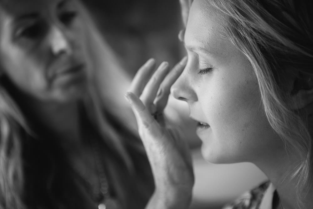 Black and white image of bride having her make up done at The Wheatsheaf Inn