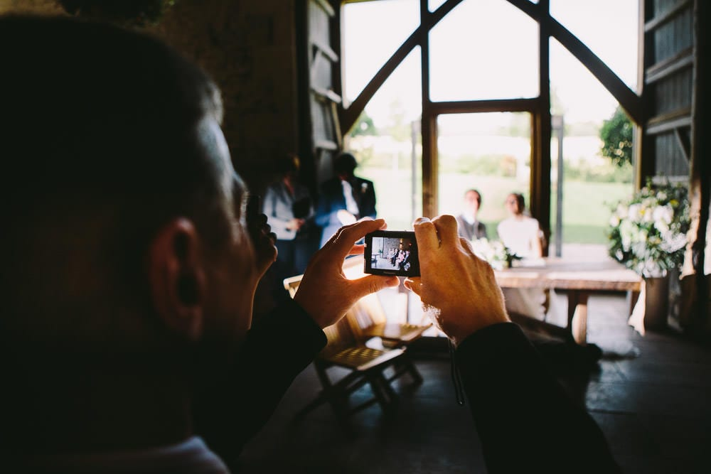 Guest taking a photo of the bride and groom during the ceremony at Cripps Stone Barn