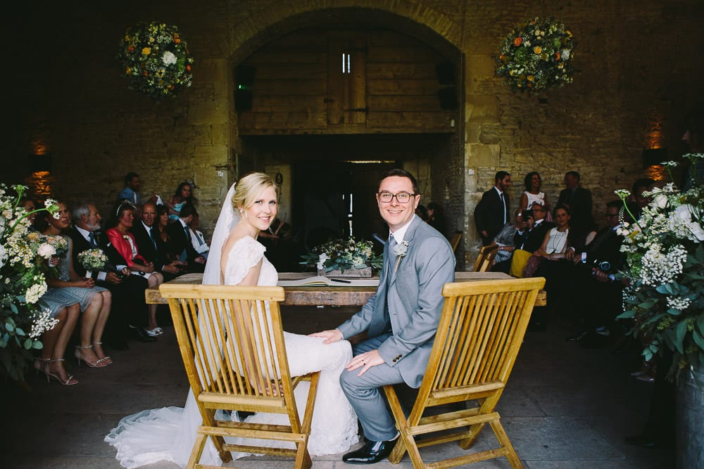 Bride and groom seated after signing the register at Cripps Stone Barn