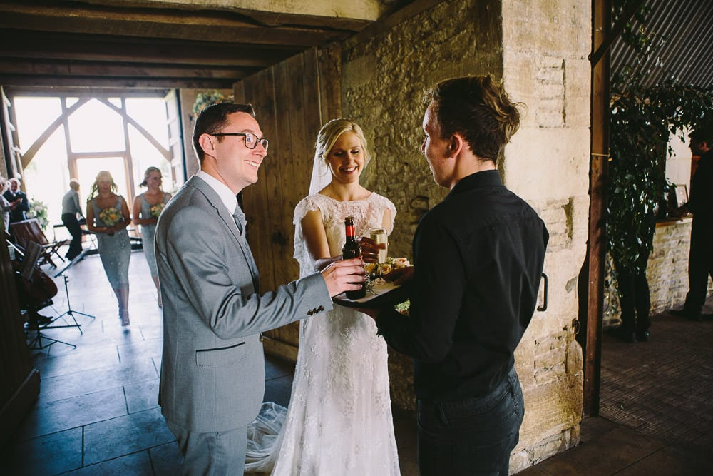 Bride and groom being handed a glass of champagne after exiting the ceremony at Cripps Stone Barn