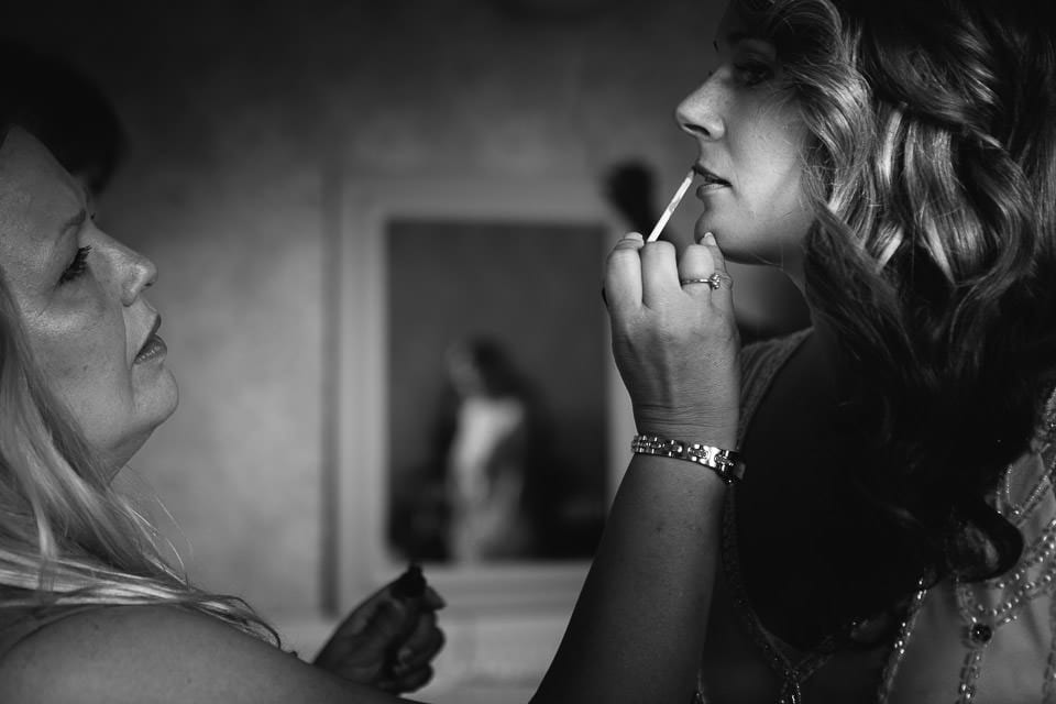 Black and white image of bride having her lipstick applied