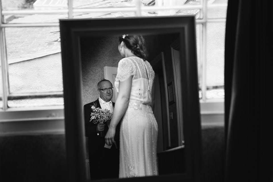 Black and white image of bride and her father in mirror